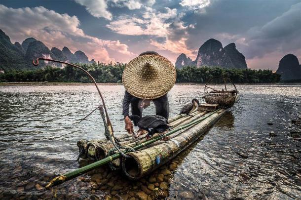 Pescador y pájaro cormorán al atardecer. (alexshot / Adobe Stock)