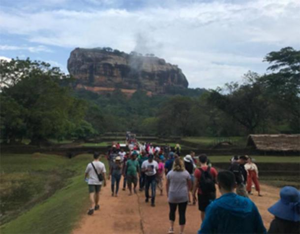 Author (far left) approaching Sigiriya. Working your way through the complex of masterfully crafted gardens and selfie-sticks that surround the giant citadel is just part of the fun. (F. Burnand / Photo courtesy of the author)