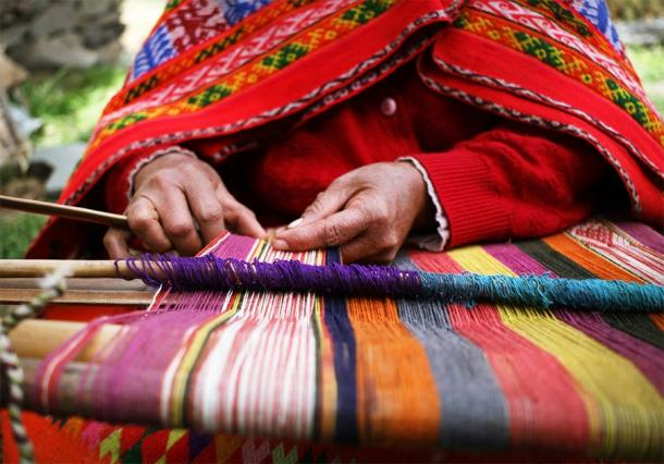Close up of an indigenous Peruvian woman weaving a traditional textile near Machu Picchu. (Shannon / Adobe Stock)