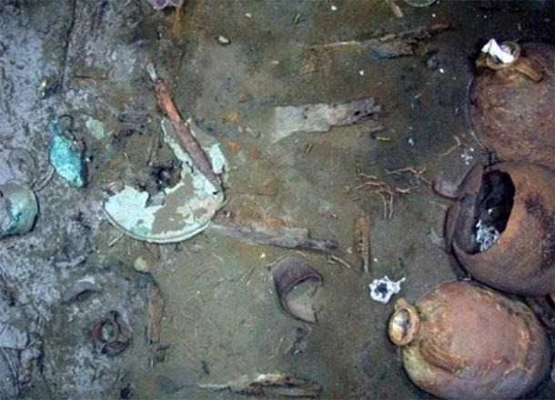 An iron shield and copper shield submerged in mud with other items from the Ottoman wreck. (©Enigma Recoveries)