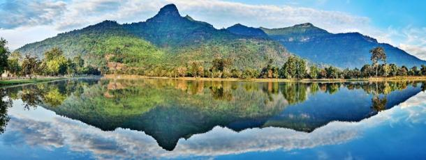 Sacred lingam-shaped Phou Khao mountain reflects in the baray (irrigation pond) of the Vat Phou temple complex