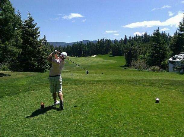 A modern golfer taking a tee shot to begin a round of golf.