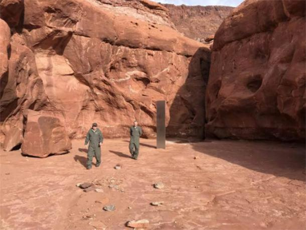 Officials walking away from the bizarre metal monolith discovered in Utah. (Utah Department of Public Safety)