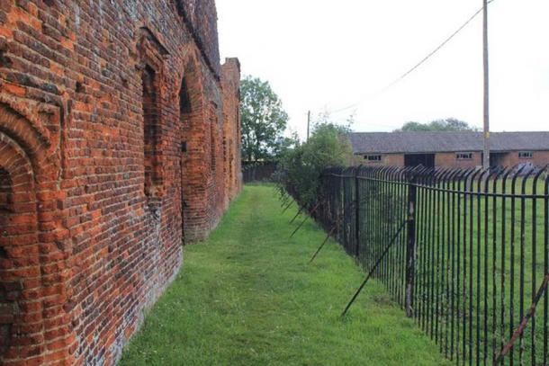 Someries Castle is situated in the middle of Someries Farm, and is closely surrounded by stout metal railings, making wide shots of the ruins very difficult. This picture shows the nature of the gap around the sides, and the proximity of the farm buildings. (David P Howard / CC BY-SA 2.0)