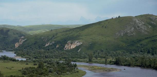 Neanderthal hunting grounds in southern Siberia — the Charysh River valley, with Chagyrskaya Cave in the center of the photo. (Image: Institute of Archaeology and Ethnography of the Siberian Branch of the Russian Academy of Sciences, Author provided)