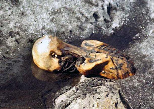 Ötzi the Iceman while still frozen in the glacier, photographed by Helmut Simon upon the discovery of the body in September 1991.