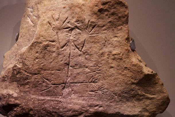 """Unearthed in the main room of the palace of Arad. It depicts two almost identical images of a man with a branch- or sheaf shaped head, one lying down and the other standing. It may represent the fertility god Tammuz or a similar deity, who died in summer and was resurrected in spring, Museum of Israel."""