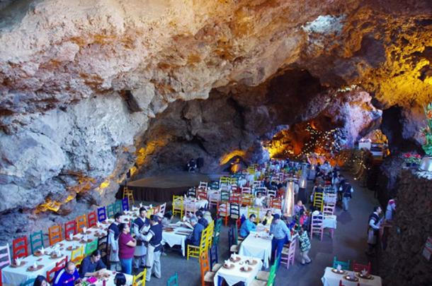 A particularly large cave, also to the East of the Pyramid of the Sun, was converted in modern times into a restaurant and events hall. The people standing and the dining furniture provide a reference for the enormous size of this chamber (Photo by author Marco M. Vigato)