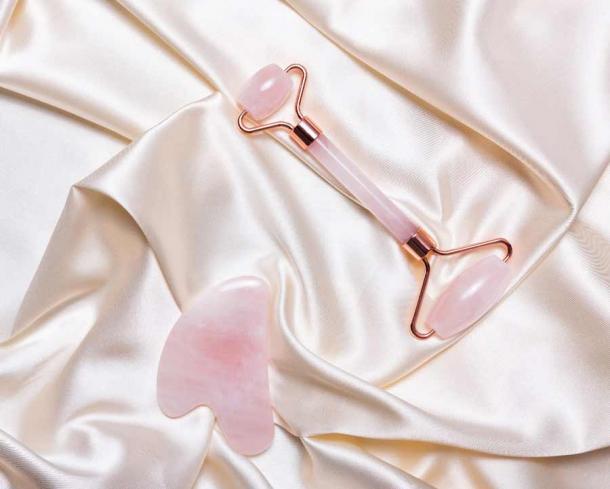 Pink jade face massage roller and Gua Sha pink quartz stone. (romanovad / Adobe Stock)
