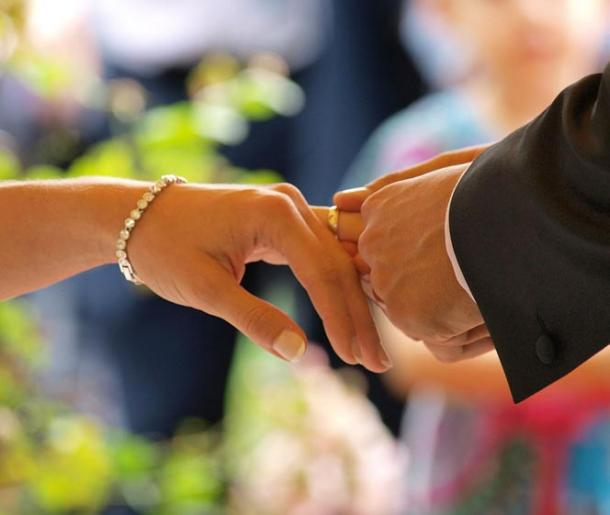 A groom placing a wedding ring on the finger of his bride during a wedding ceremony.