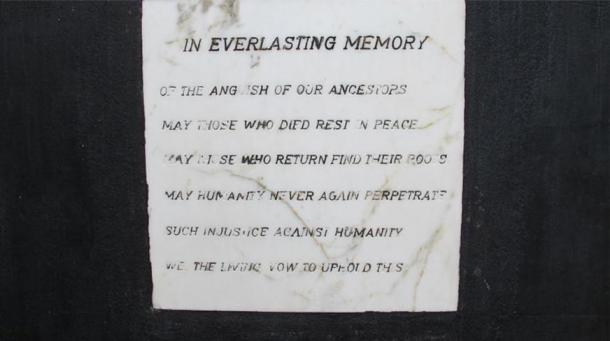 """A plaque next to the condemned dungeon door which reads: """"In Everlasting Memory of the anguish of our ancestors.  May those who died rest in peace.  May those who return find their roots. May humanity never again perpetrate such injustice against humanity. We, the living, vow to uphold this"""