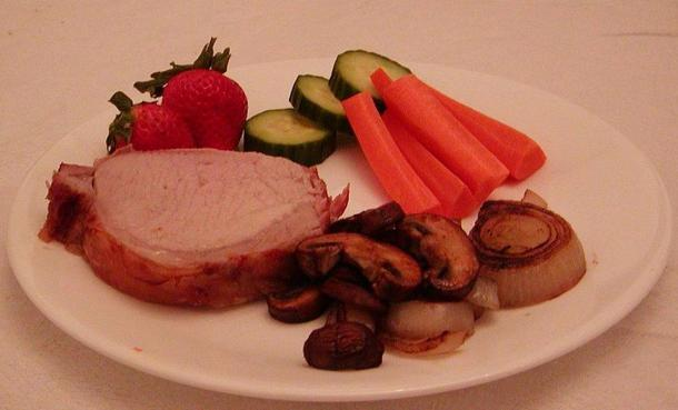 Paleolithic-style dish: Roast pork with cooked and raw vegetables and fruit.