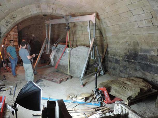 Lifting and positioning of the Bronze Age stone map that was luckily rediscovered in 2014 in the chateaux cellar. (Clément Nicolas, Yvan Pailler / Inrap)