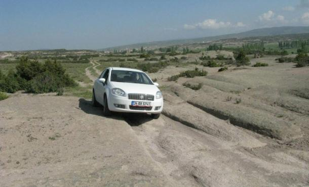 The prehistoric mysterious vehicle tracks as found in the Phrygian Valley of Turkey, with a modern car for scale.