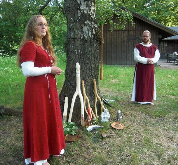 In Sweden, a priestess and a priest perform a ceremony during an annual Asatru thing (meeting). Under the tree are images of Norse gods Thor, Frigg, Freyr, Freya and Forseit with a ceremonial hammer, a drinking horn and an oath ring. Hanging on the birch tree, which is sacred to the goddess Frigg, hangs a birch trumpet.