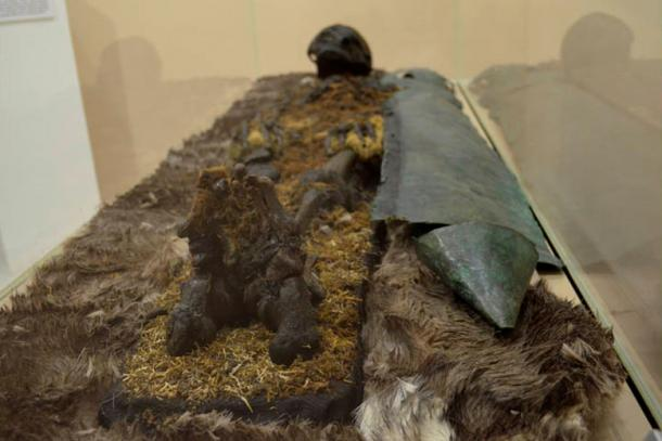 'A red-haired man was found, protected from chest to foot by copper plating. In his resting place, was an iron hatchet, furs, and a head buckle made of bronze depicting a bear.'