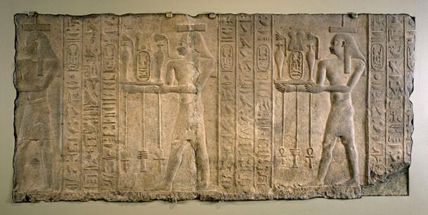 A relief from the time of Nectanebo II's reign showing gods carrying flowers and drinks for the pharaoh.
