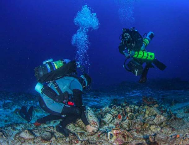 Research scientist Dr. George Koutsouflakis moves an amphora from the Antikythera shipwreck cargo. (Greek Ministry of Culture)