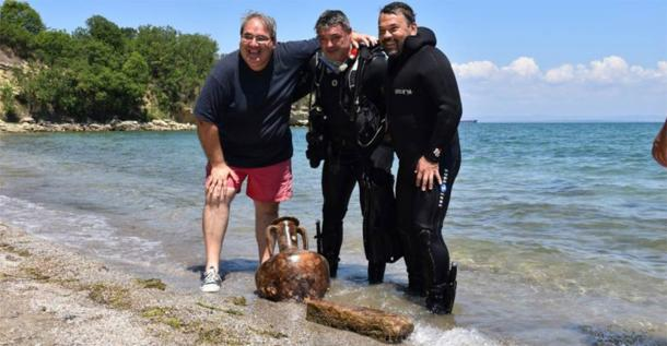 Elated researchers posing with a perfect amphorae and a worked stone found underwater, just off the coast of Cape Chiroza. (Burgas Municipality)