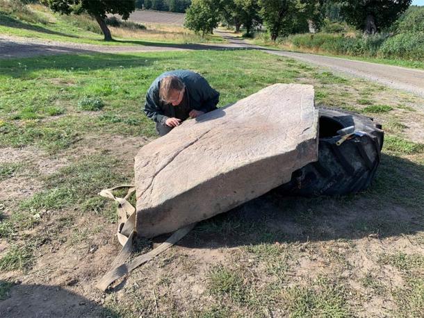 The runologist, Magnus Källström from the Swedish National Heritage Board, studies the newly discovered Viking runestone. (Ingemar Lundgren / Västervik Museum)