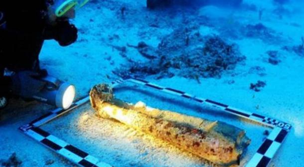 Examining the sculpture's legs underwater.