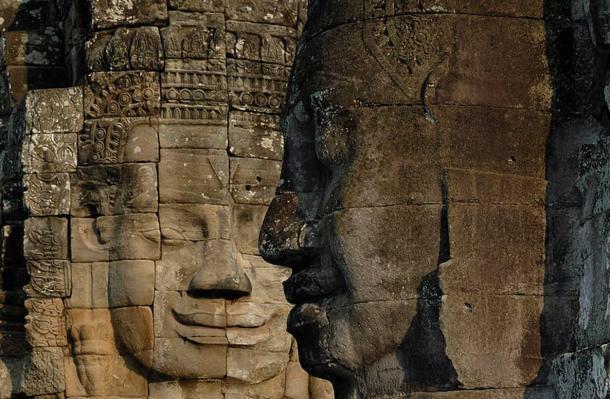 La piedra serena enfrenta mirando desde las muchas torres en el templo Bayon, Camboya.