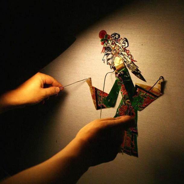 Hands manipulate a shadow puppet.