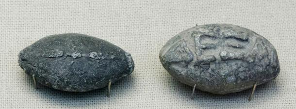 "Ancient Greek sling bullets with engravings. One side depicts a winged thunderbolt, and the other, the Greek inscription ""take that"" in high relief."