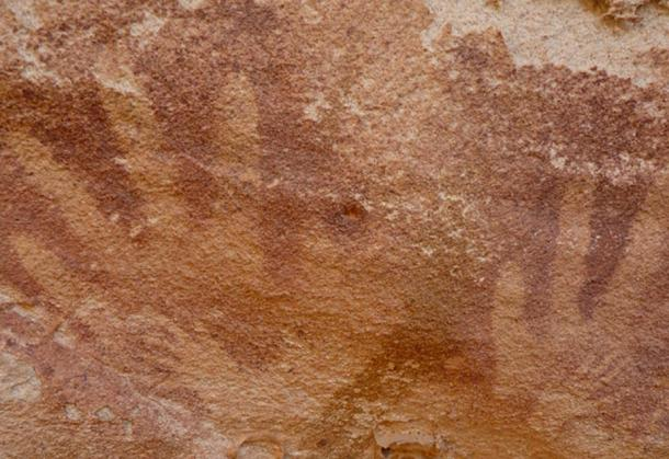 """Image of tiny """"handsprints"""", which may have been made by reptiles, inside adult human handprints at the Wadi Sura II rock shelter."""