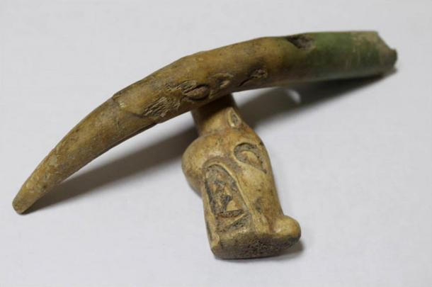 The cheek piece is decorated with carving - on one end, the head of a snow leopard or wolf, and on the other a griffin.