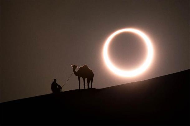 Annular solar eclipse in desert with a silhouette of a dromedary camel. Liwa desert, Abu Dhabi, United Arab Emirates. (Kertu /Adobe Stock)