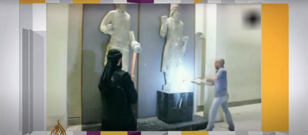 ISIS soldiers in the Museum of Mosul destroying ancient Nineveh artifacts with sledgehammers in 2015. (Aljazeera / Screenshot)