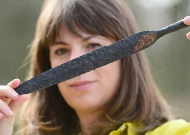 Map Archaeological Practice Ltd staff member Sophie Coy holds a spear head that was found at the site.