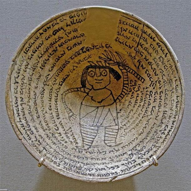 Protective spells on an ancient Jewish occult incantation bowl from the Sassanid Empire. These bowls were buried upside down below the structure of the house or on the land of the house to trap demons. The center of the inside of the bowl depicts Lilith, or the male form, Lilit. Surrounding the image is a spiral form incantation inscribed in Jewish Babylonian Aramaic, Syriac, Mandaic, Middle Persian, and Arabic. (Marie-Lan Nguyen (2011) / CC BY-SA 2.5)