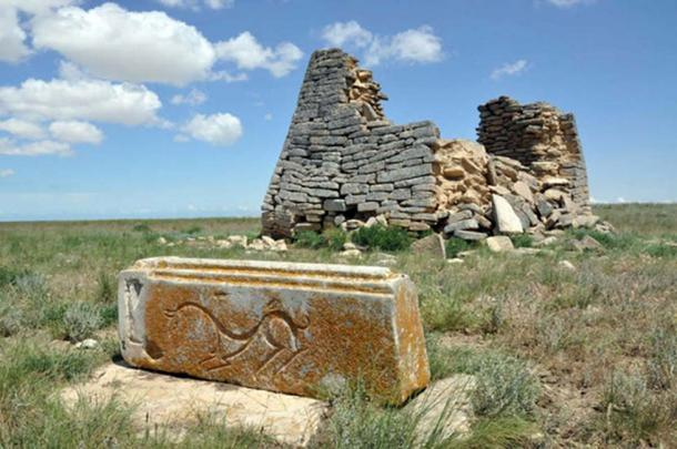 A stone structure and a carved stone that shows an animal.