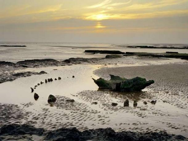 Seahenge during sunset, after some of the timber had been removed by archaeologists for testing and preservation. (Historic England)