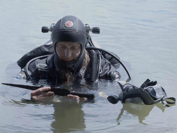 One of the Polish archaeologists surfacing with just one of the 20 artifacts found on the lake bottom, including the rare medieval sword. (Nicolaus Copernicus University)