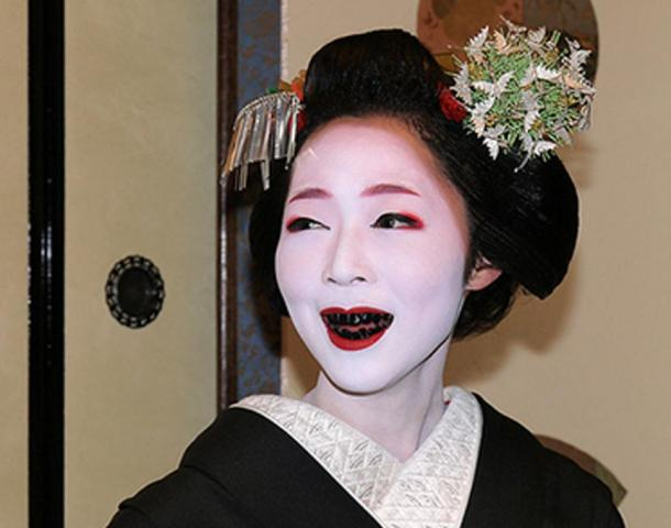 A woman with teeth stained black by the practice of Ohaguro.