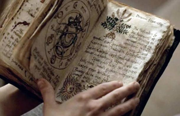 Person holding an ancient grimoire—a textbook of magic.