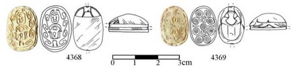 In the tomb labeled A2, archaeologists found two Egyptian-like amulets, known as scarabs.