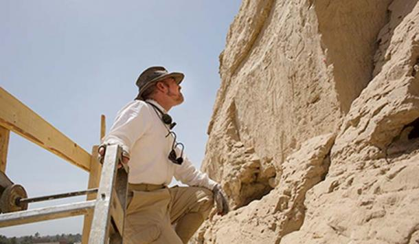 From the top of a tall scaffold, Yale Egyptologist John Darnell examines large hieroglyphs discovered along an ancient trade route. (Yale photo)