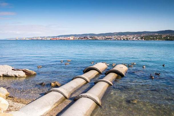 Concrete tubes going into the sea. (eunikas / Adobe Stock)