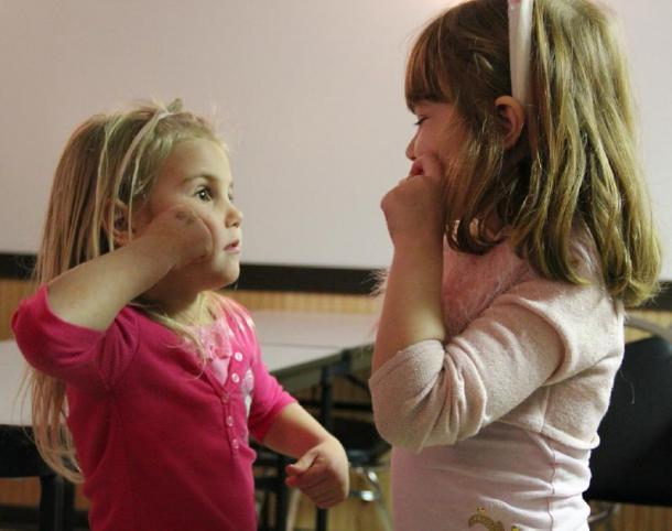 Two girls communicating via unspoken language. (Mr. Stradivarius / CC BY-SA 2.0)