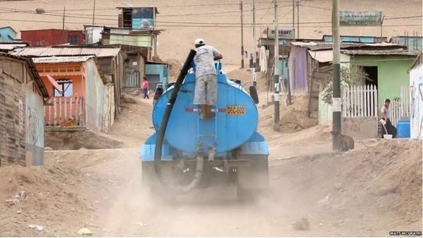 Paying for water delivered by truck is part of the daily routine for many inhabitants in Peru.