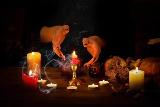 Depiction of witch making passes over candles and wax on an altar in the dark. (junky_jess / Adobe stock)