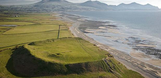 An aerial photograph of Dinas Dinlle Iron Age Hill Fort from the north (suffering from coastal erosion); Gwynedd, Cymru / Wales. Cromlechs & Ancient Sites. (CADW/Visit Wales/CC BY SA 3.0)
