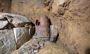 "A cuirass known as a ""tanko"" and preserved in excellent condition, and a stone coffin, left, have been unearthed in Shibushi, Kagoshima Prefecture."