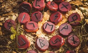 Red runes carved from wood on the ground. There are 24 runes in the Elder Futhark.