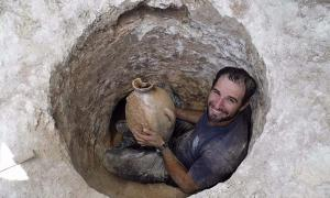 David Tanami, an Israel Antiquities Authority archaeologist, works his way into the narrow tomb opening to bring out a jar at a Canaanite burial site near Jerusalem's Biblical Zoo.