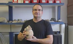 Haifa University Prof. Danny Rosenberg holds the 7,200-year-old model clay grain silo found at Tel Tsaf in the Jordan Valley.